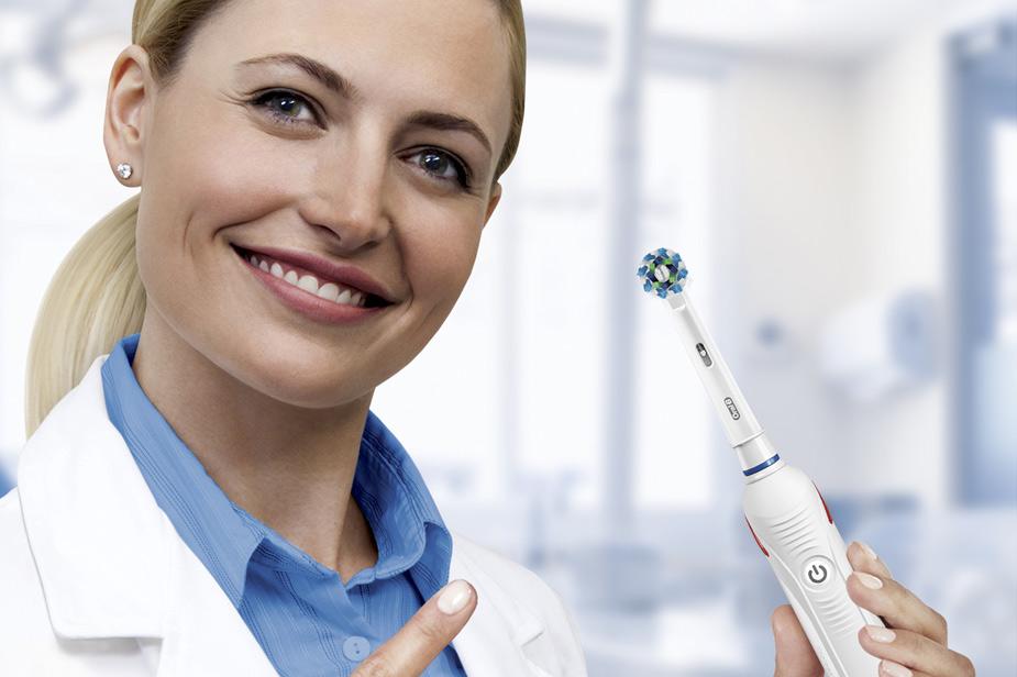 Električna zobna ščetka Oral B zobozdravnica drži v roki