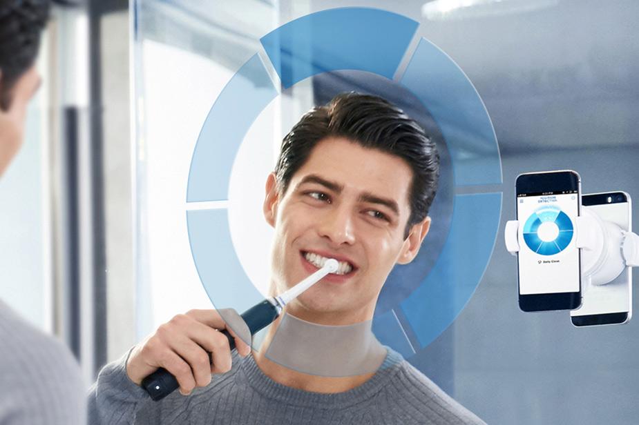Moški z električno zobno ščetko Oral B ščetka zobe