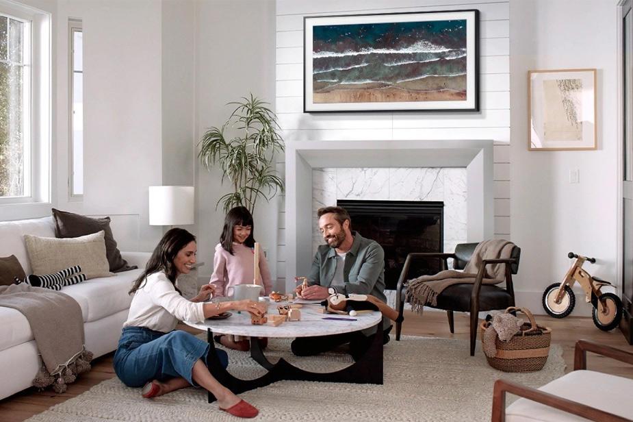 Samsung Frame tv s črnim okvirjem nad kaminom pred njim družina