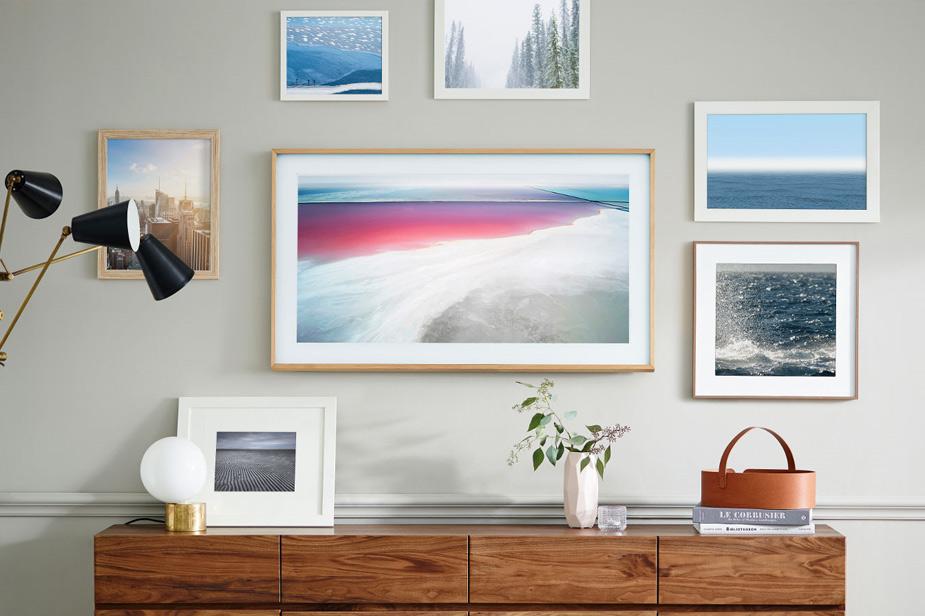 Samsung Frame tv s svetlo rjavim okvirjem med fotografijami na steni