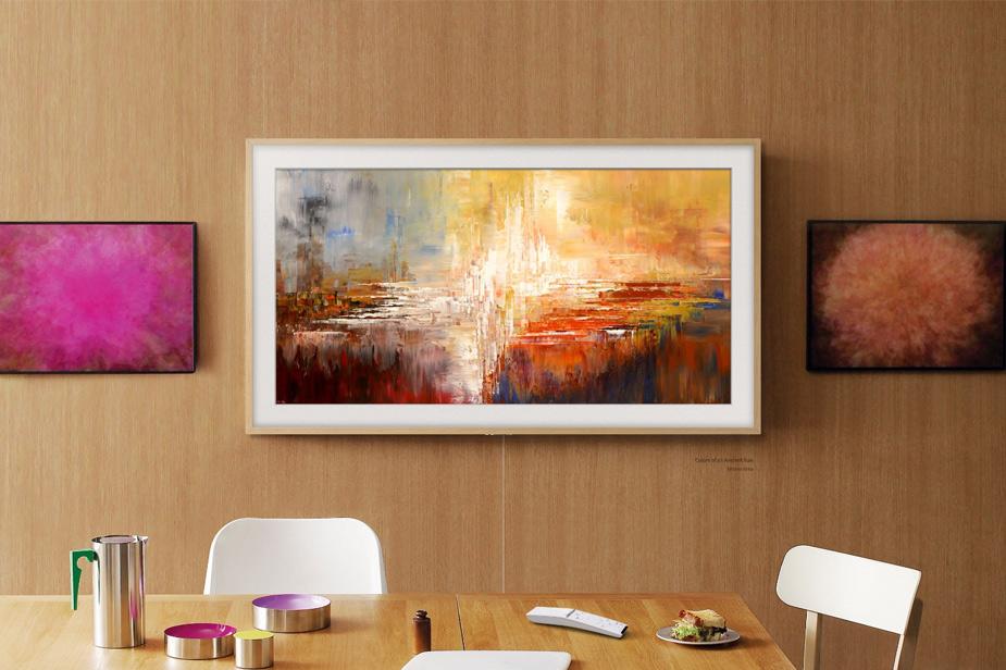 Samsung Frame tv v svetlo rjavem okvirju na leseni steni sejne sobe med slikami