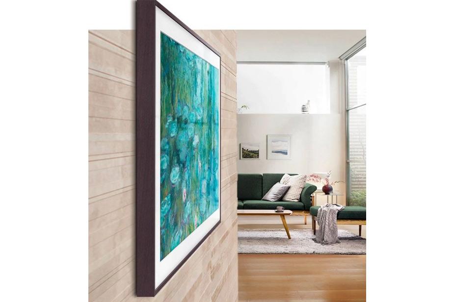 Samsung Frame tv v temno rjavem okvirju s pogledom na kavč v dnevni sobi